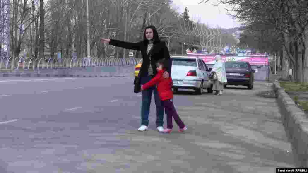Waving for a taxi with her child on a street in Dushanbe