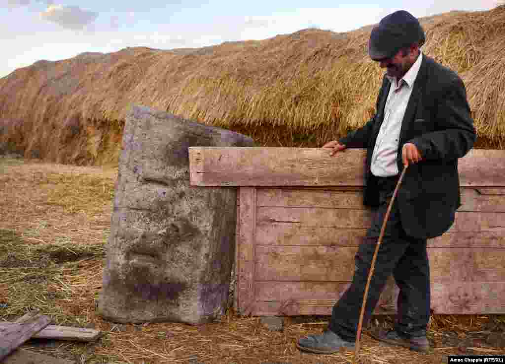 A local from the village of Oguzlu shows a khachkar that is being used as part of a fencepost. The men of the village say they found two khachkars when excavating the foundations of a house in the village.