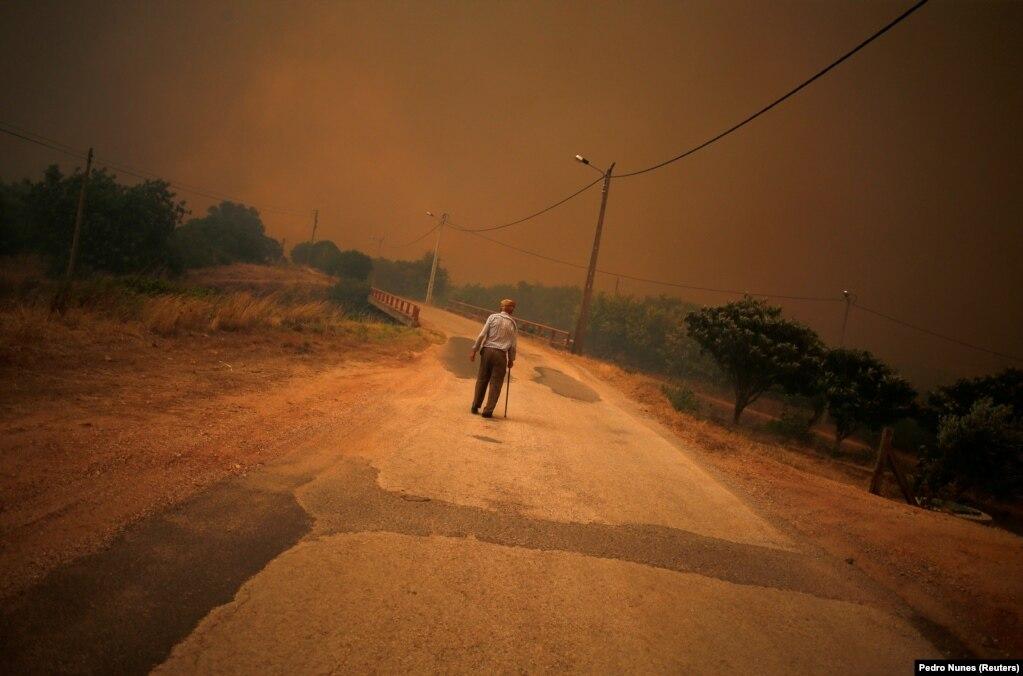 Një njeri ecën në një rrugë, teksa zjarri që ka kapluar Portugalinë, afrohet pranë Pedreira, që gjendet pranë qytetit Silves.