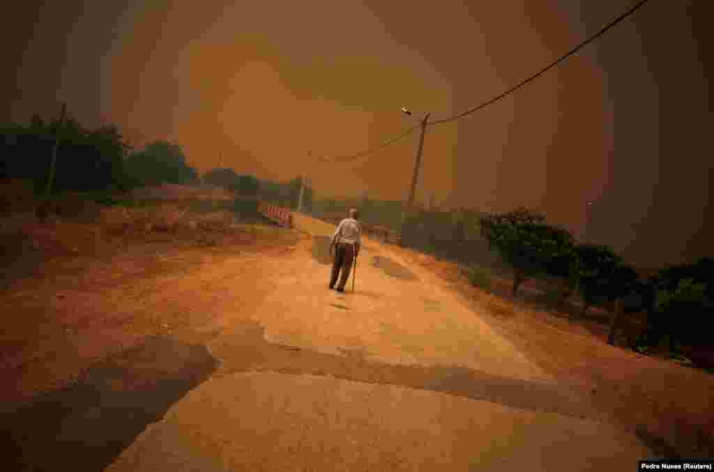 A man walks on a road as a wildfire approaches Pedreira, near Silves in Portugal. (Reuters/Pedro Nunes)