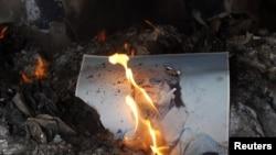 Լիբիա - Ընդդիմադիրները այրում են երկրի ղեկավար Մուամար Քադաֆիի դիմանկարը, Բենգազի, 28-ը փետրվարի, 2011թ.