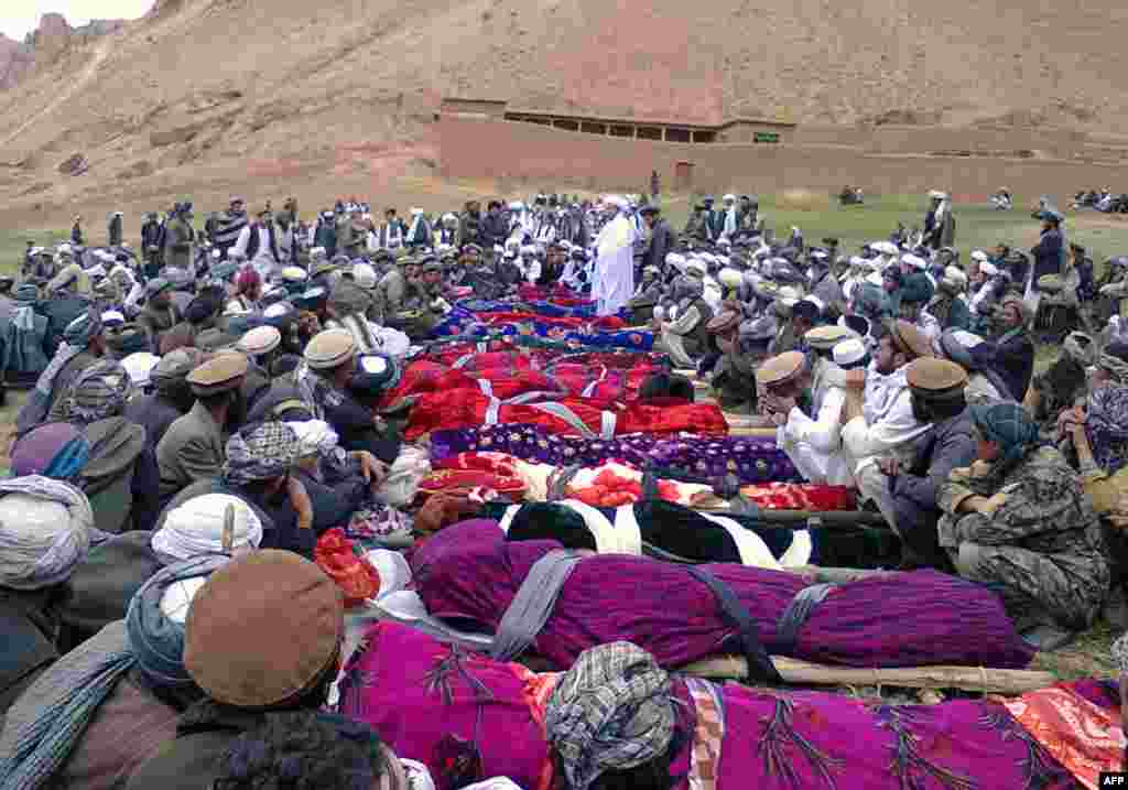 Mourners sit next to the bodies of miners who died in a mine collapse in Ruyi Du Ab district of Afghanistan's Samangan Province. At least 28 died in the tragedy. (AFP)
