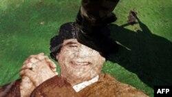 Ливиялик исëнчи 42 йиллик диктатор суратини топтамоқда.