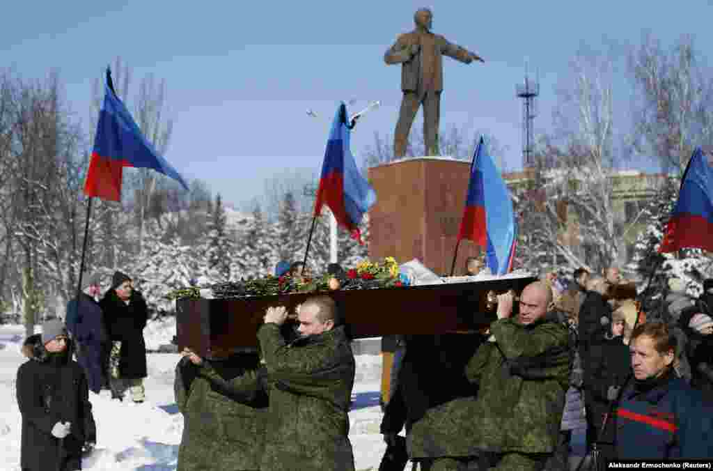 UKRAINE -- Men carry the coffin of one of the four fighters of the Luhansk separatist forces who were killed last week in fighting against Ukrainian government troops, during a funeral at a cemetery in the town of Kadiyivka, Luhansk Region, February 10,