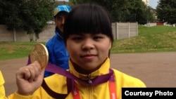 Қазақстандық ауыр атлет Зүлфия Чиншанло Лондон олимпиадасында алған алтын медальді көрсетіп тұр. Ұлыбритания, 29 шілде 2012 жыл.
