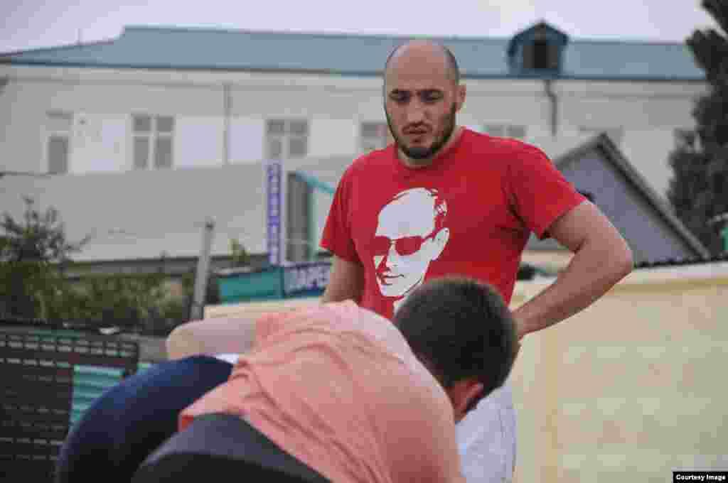 Тренер в футболке с портретом Владимира Путина строг и внимателен с ученикам