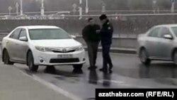 Türkmenistanda ýol polisiýasy sürüjiniň resminamalaryny barlaýar.