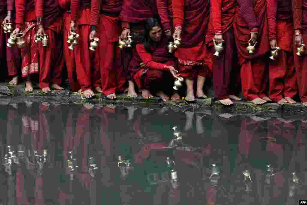 Hindu devotees wait to fill pots with water from the Bagmati River at the Pashupatinath Temple during the monthlong Swasthani festival in Kathmandu. (AFP/Prakash Mathema)