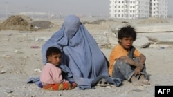 A burqa-clad woman begs with her children near a newly constructed building in Kabul.