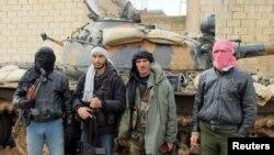 Байцы Вольнай сырыйскай арміі на фоне танка, адбітага ва ўрадавых войскаў. Эль-Кусаір, Сырыя. 23 лютага, 2012