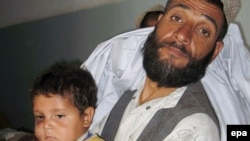 An Afghan man holds a child reportedly injured in an ISAF air strike in Herat Province on July 17