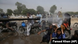 A volunteer sprays water on people to keep them cool as temperatures reached 44 Celsius in Karachi on May 21.
