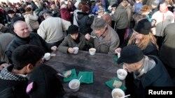 Люди, пришедшие за бесплатным супом, обедают в историческом центре Праги. 4 декабря 2013 года.