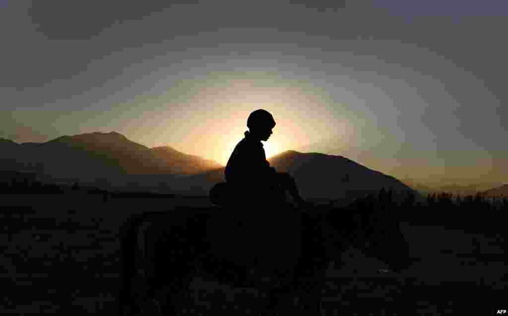 An Afghan boy rides a horse as the sun sets on the Nadir Khan hilltop overlooking Kabul. (AFP/Shah Marai)