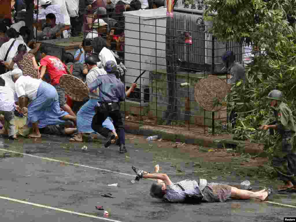 A Japanese videographer, sprawled on the pavement, fatally wounded during a street demonstration in Myanmar, Kenji Nagai of APF tries to take photographs as he lies injured after police and military officials fired upon and then charged at protesters in Yangon's city centre September 27, 2007. Nagai, 50, a Japanese video journalist, was shot by soldiers as they fired to disperse the crowd. Nagai later died. REUTERS/Adrees Latif
