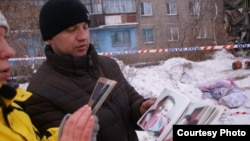 Алексей Алексеенко, родственник погибших в результате обрушения дома, показывает фото погибшей девушки с полугодовалым ребенком. Шахан, 2 января 2017 года.