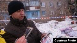 Туыстары қаза тапқан Алексей Алексеенко мерт болған адамдардың суретін көрсетіп тұр. Шахан, 2 қаңтар 2017 жыл.