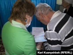 Социальный работник (слева) помогает престарелому человеку заполнить избирательный бюллетень на досрочных президентских выборах в доме ветеранов. Фото репортера Азаттыка. Алматы, 26 апреля 2015 года.