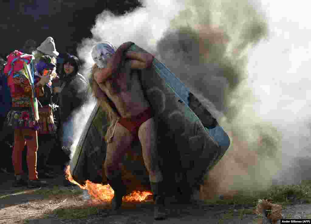 A masked participant carries a burning mattress during the ancient carnival of Zubieta in the northern Spanish province of Navarra. (AFP/Ander Gillenea)