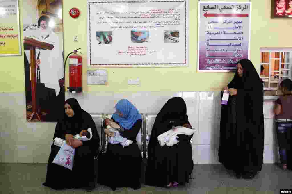 Women wait with their babies at a health clinic in Sadr City.