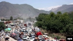 Residents of the restive Swat Valley flee on May 10 after a curfew was temporarily lifted to allow people to escape the intensifying conflict.
