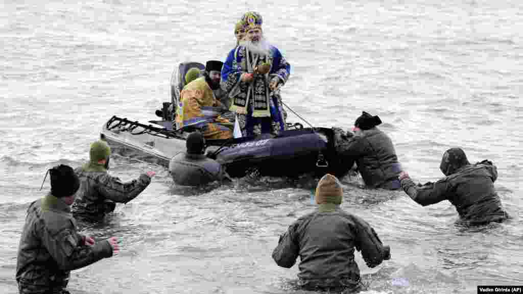 Military divers walk to a boat carrying Archbishop Teodosie, a Romanian cleric, during an Epiphany service in Constanta, Romania. (AP/Vadim Ghirda)
