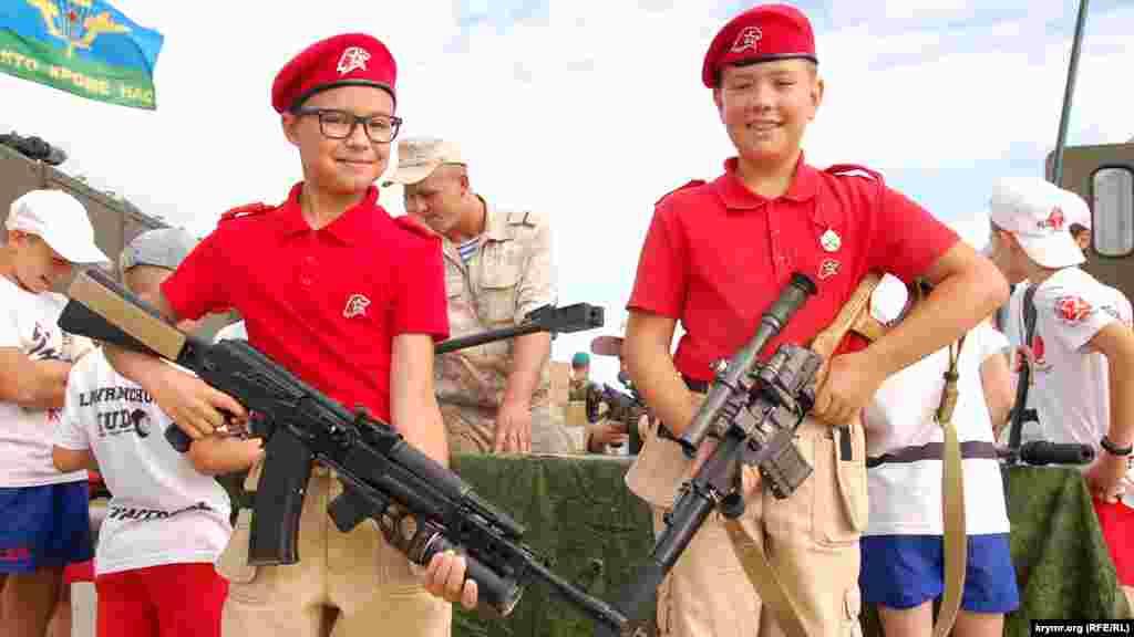 Два мальчика из движения «Юнарамия» с российским стрелковым оружием на праздновании Дня ВДВ в Севастополе