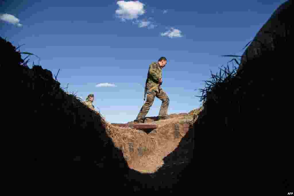 A Ukrainian serviceman walks past a trench on the front line near Luhansk during shelling on August 26. (AFP/Oleksandr Ratushniak)