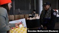 Сотрудник агентства транпортной безопасности получает продуктовое пособие в центре помощи госслужащим. Нью-Йорк, 22 февраля