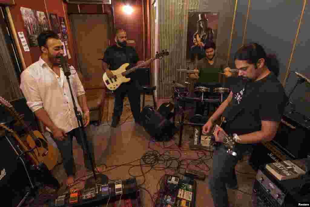 Lead guitarist and songwriter Khurram Waqar (right), vocalist Umair Jaswal (left), bass guitarist Rahail Siddiqui (second from left), and drummer Asfendyar Ahmad of the rock band Qayaas rehearse at a private studio in Islamabad. The band members say that the current security situation has hampered Pakistan's music scene. Most of the band's performances are at schools, colleges, and private festivals.