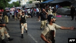 Pakistani paramilitary soldiers gather at the site of a bomb blast in Karachi on July 10.
