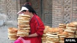 Tajikistan - A girl is selling bread in a market in Panjakent city, Apr2008