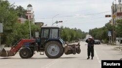 Сотрудник сил безопасности в городе Актобе блокирует движение автомашин. 10 июня 2016 года.