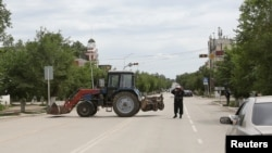 Kazakh police officer blocks a street near the site of a fire exchange between Kazakh security forces and suspected militants linked to deadly attacks this week on a national guard base and several firearms shops, in Aqtobe, on June 10.