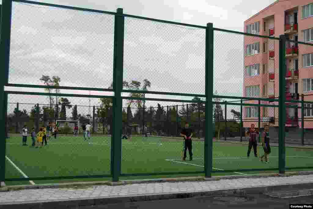 Дети играют в футбол на недавно построенном стадионе