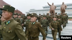 North Korean soldiers visit the bronze statues of North Korea founder Kim Il Sung (left) and late leader Kim Jong Il at Mansudae in Pyongyang on April 15.