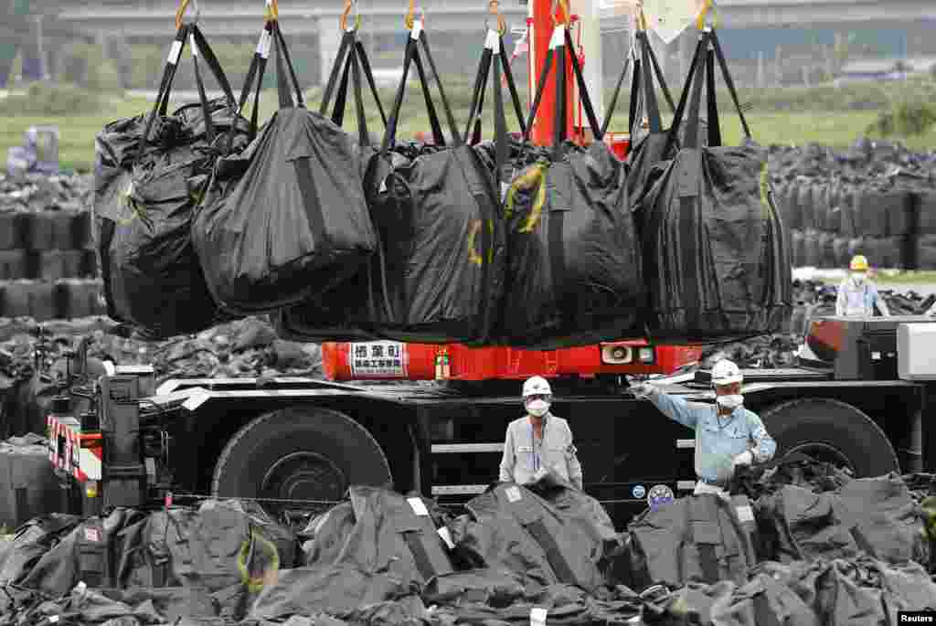 Workers move bags of contaminated soil and debris to a storage site in Naraha.