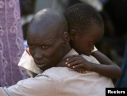Мужчина и его сын, беженцы-динка, на территории миссии ООН в Джубе