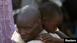 Мужчина и его сын, беженцы-динка, на территории миссии ООН в Джубе.