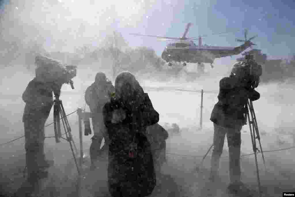 Reporters are whipped by snow as U.S. President Barack Obama departs via the Marine One helicopter from the White House. (Reuters/Jonathan Ernst)