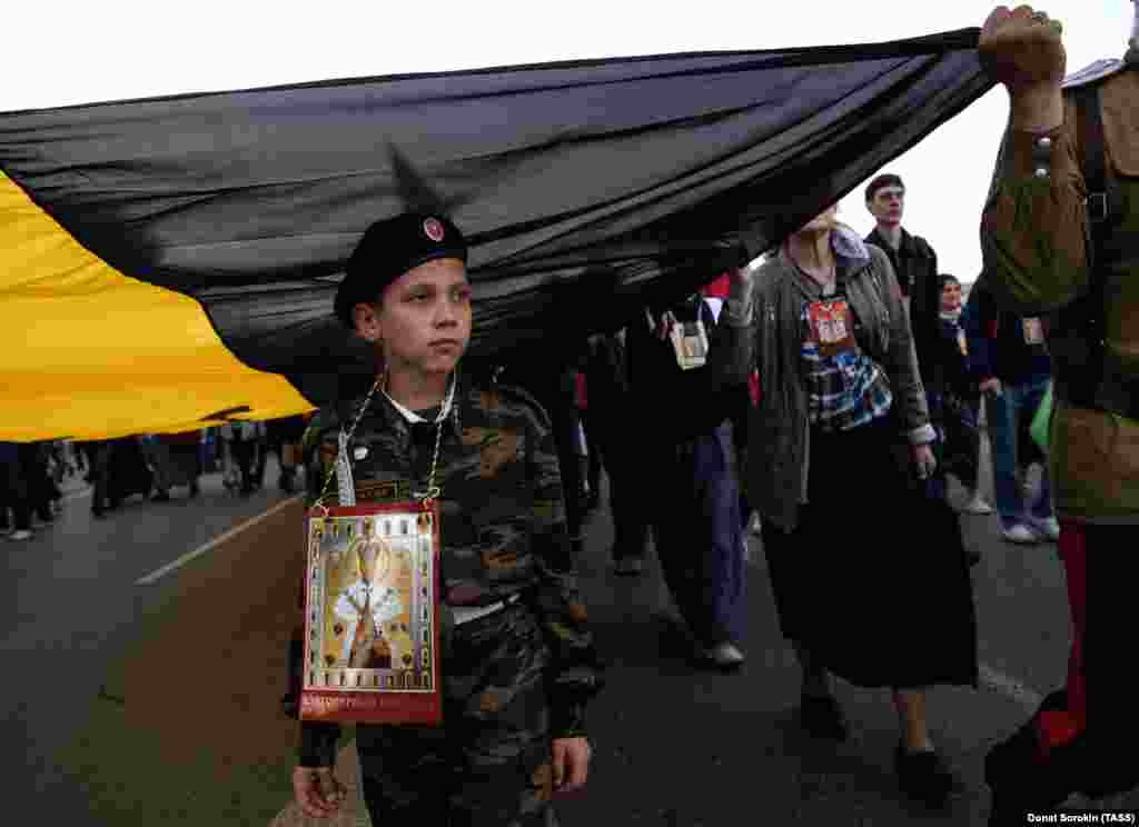 A boy walks beneath the yellow, black, and white flag of Imperial Russia.