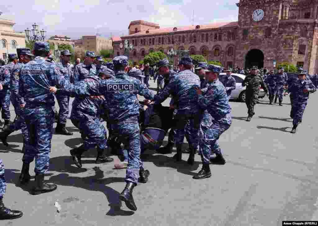 A policeman kicks a demonstrator as he is dragged into a police van in Yerevan's Republic Square.