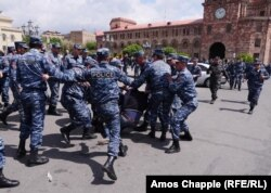 A policeman kicks a demonstator as he is dragged into a police van in Yerevan's Republic Square on April 22.