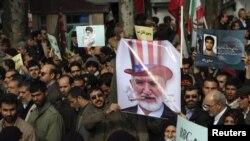 Оппозиция акциясы кезінде мерт болған студентті жерлеушілер реформашыл оппозиция жетекшісі Мехди Каррубидің суретін келемеждеп салған. Тегеран, 16 ақпан 2011 жыл. (Көрнекі сурет)