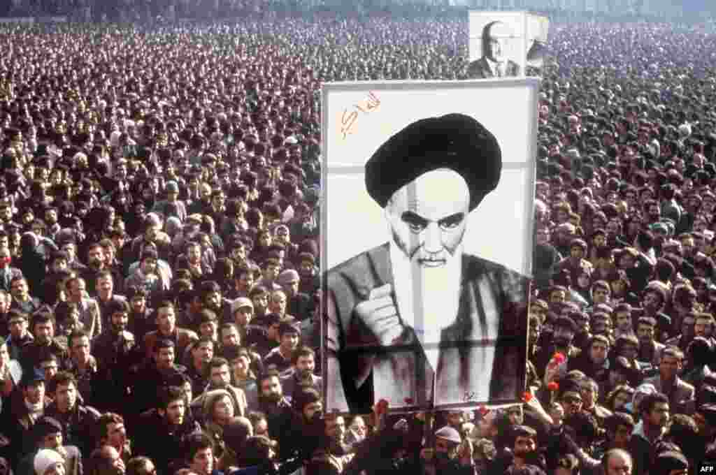 Anti-Shah protests continue to grow as demonstrators hold a poster of Ayatollah Ruhollah Khomeini during mass protests on January 1, 1979.  Khomeini had spent 14 years in exile. Cassette tapes of speeches by the 76-year-old Khomeini were smuggled into the country, fueling the unrest.