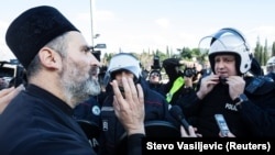 A Serbian Orthodox priest speaks with a riot policeman on a bridge near parliament, ahead of a vote on a bill on religious organizations in Podgorica on December 26.