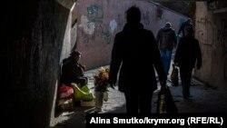 Пенсионерка продает цветы в подземном переходе