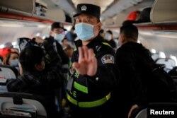 """Үрүмчү аэропортунда полиция кызматкерлери учакка кирип, """"Рейтер"""" агенттигинин кабарчыларын терминалга биринчилерден болуп чыгарып кеткен. 5-май, 2021-жыл"""
