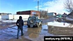 """Нұр-Сұлтанның шетіндегі """"Кирпичный"""" елдімекенінде су басқан лай жолмен кетіп бара жатқан адам мен жеңіл автокөлік."""