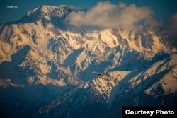Самолет летит на фоне гор. Фото Павла Михеева
